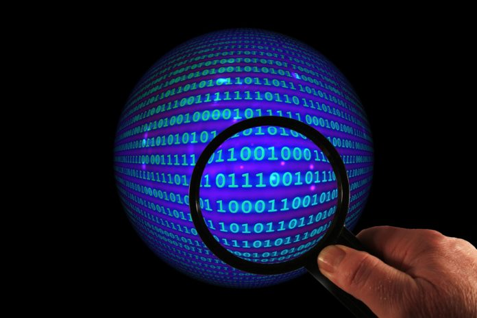Data Discovery Represented by Magnifying Glass Over Globe of Binary Code Data.