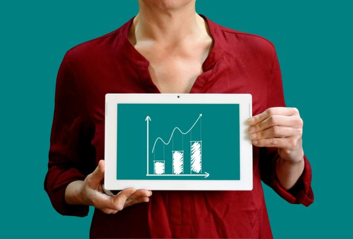 Woman holding an image of a bar graph to illustrate data visualization.