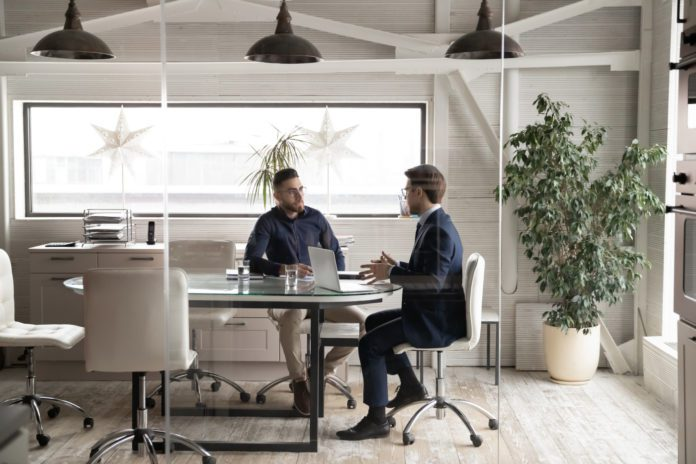 A rep and an employee meet around a conference room table.
